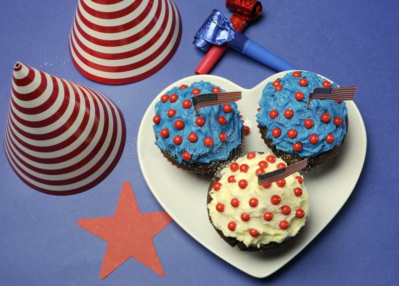 Quarto quarto della celebrazione del partito di luglio con i bigné del cioccolato ed i cappelli rossi, bianchi e blu del partito immagini stock