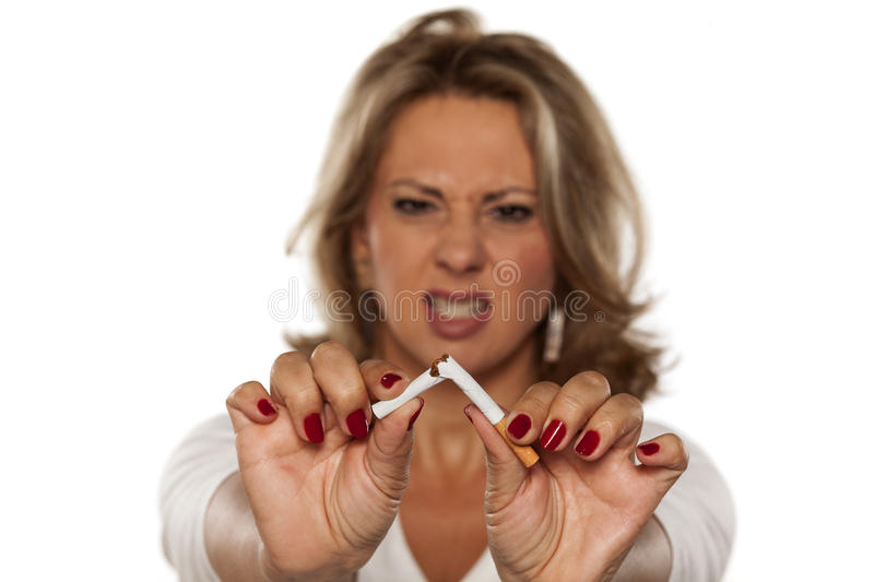 I am quitting smoking today. Angry middle-aged woman breaking a cigarette stock photography