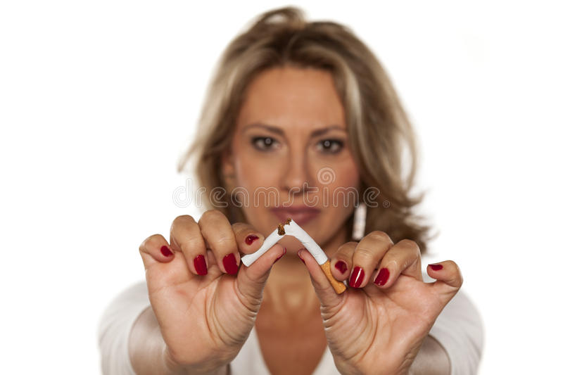I am quitting smoking today. Happy middle-aged woman breaking a cigarette stock photos
