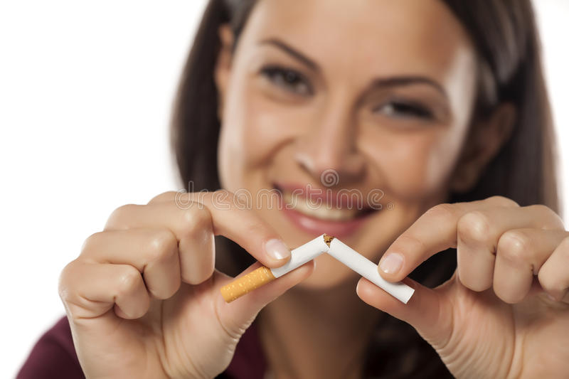 I am quitting smoking today. Happy young woman breaking a cigarette stock photo
