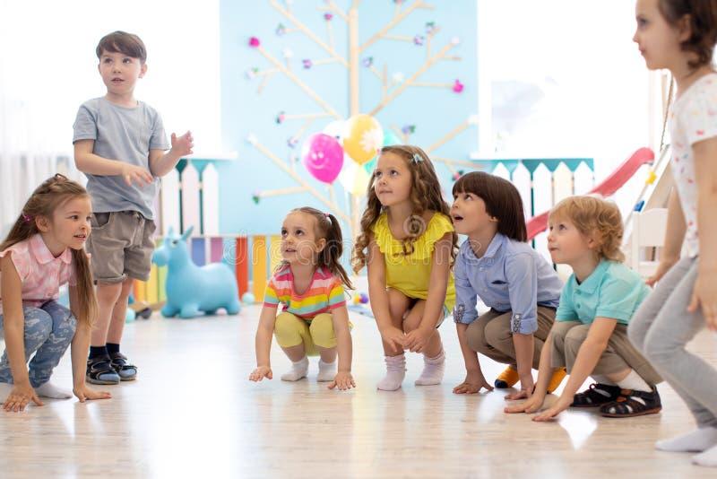 I ragazzi e le ragazze prescolari dei bambini occupano il gioco nell'asilo fotografia stock