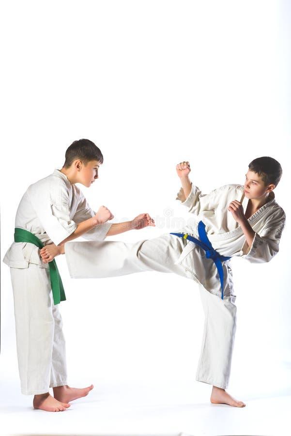 I ragazzi in kimono durante il karatè di addestramento si esercita su fondo bianco fotografia stock