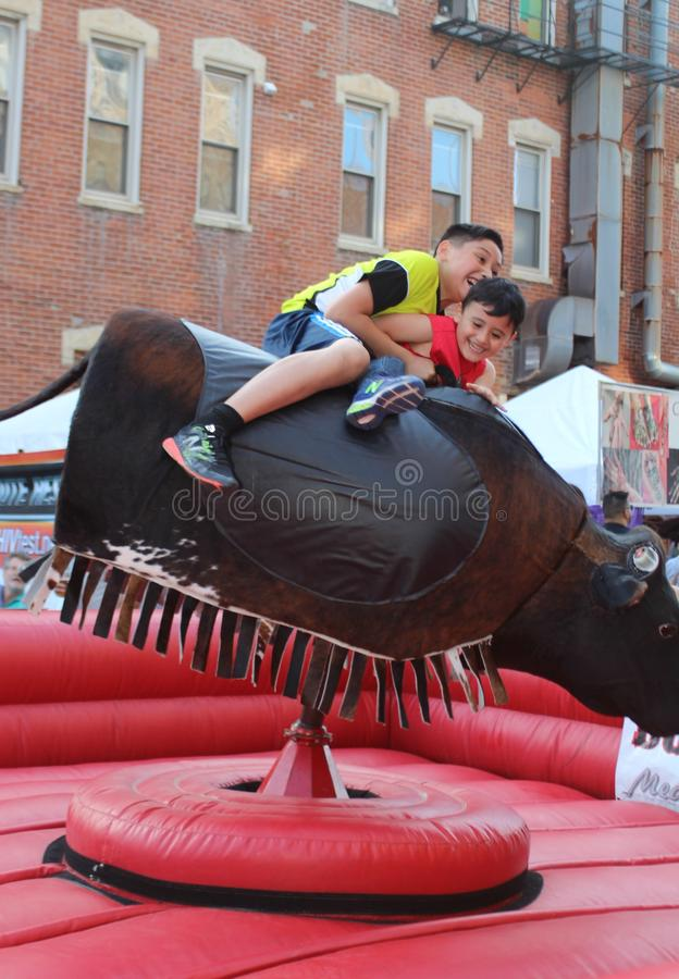 I ragazzi sorridenti guidano un toro meccanico ad un festival messicano della via in Chicago fotografia stock
