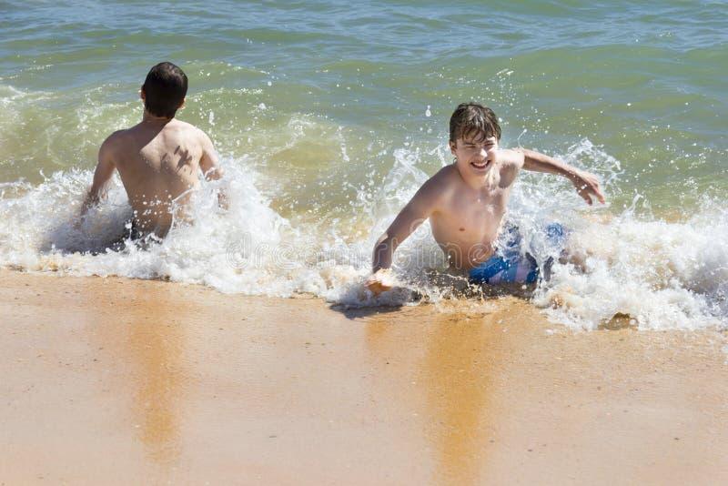 I ragazzi stanno giocando in bello mare con acqua cristallina fotografia stock