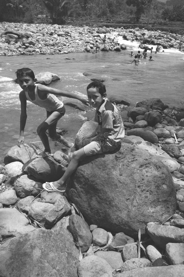 I ragazzi stanno giocando nella sponda del fiume immagine stock