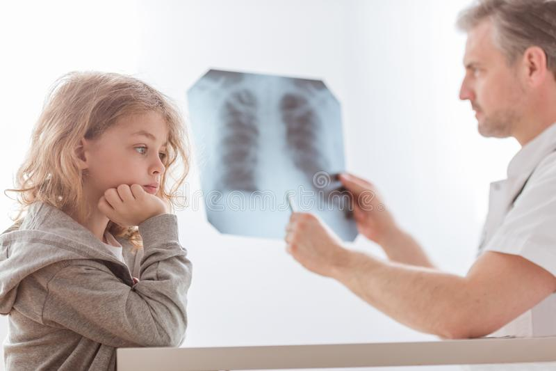 I raggi x del polmone d'esame di medico di piccolo bambino sveglio nell'ospedale fotografia stock libera da diritti