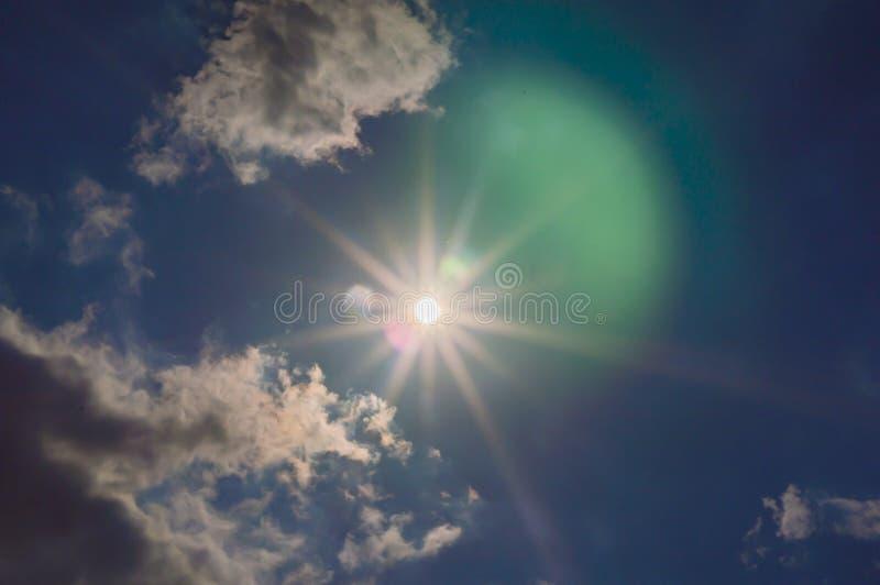 I raggi del sole attraversano le nuvole nel cielo fotografie stock libere da diritti