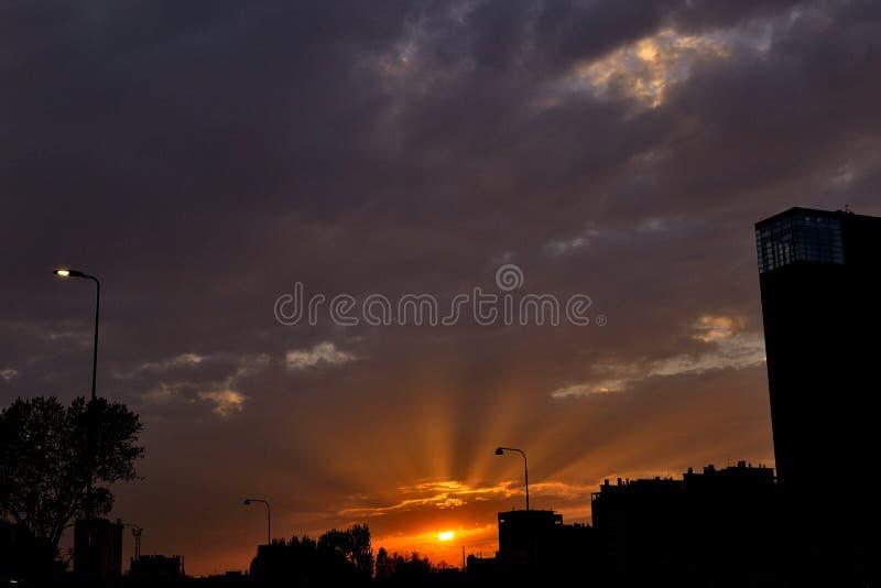I raggi del tramonto compare dietro un cielo nuvoloso fotografia stock