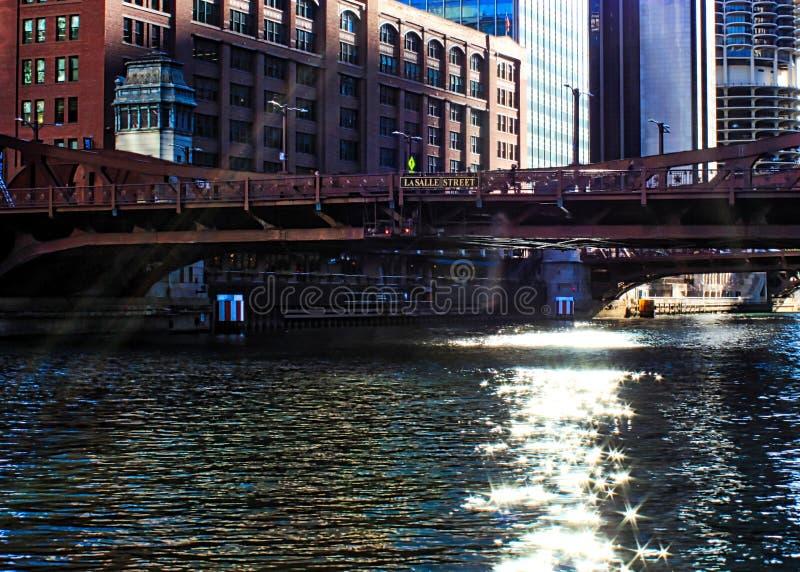I raggi di sole estendono sopra il ciclo del centro di Chicago, creante brillare stars sul fiume nel corso della mattinata immagine stock libera da diritti