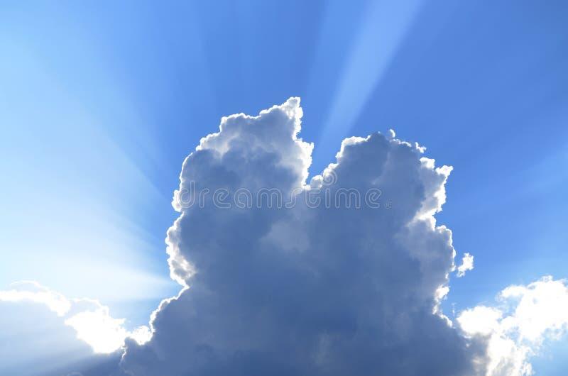 I raggi di Sun guardano fuori dietro delle nuvole di cumunus in un cielo blu fotografia stock libera da diritti