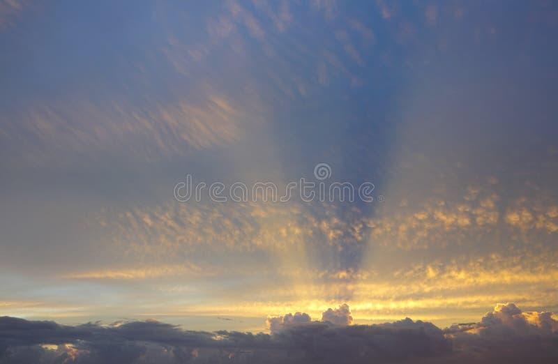 I raggi dorati del sole da dietro le nuvole allungano attraverso il cielo qui sopra immagine stock