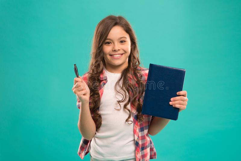 I am ready for school. Child smart kid hold pen and notepad. Girl cute happy face likes to study blue background. Child royalty free stock photo