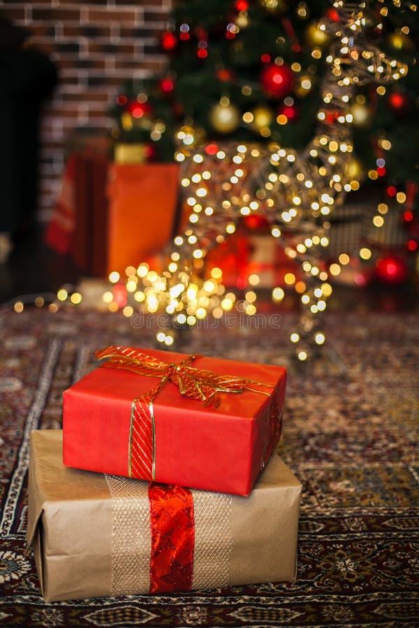 I regali di Natale avvolti in carta marrone e rossa in sottotetto, fondo con natale accende il bokeh dell'albero di Natale vago C fotografia stock libera da diritti