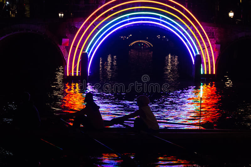 I rematori passano un materiale illustrativo in un canale sui colori di acqua dell'itinerario della barca durante il festival 201 fotografie stock libere da diritti