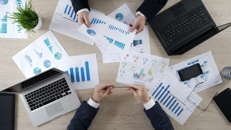 I responsabili che controllano l'affare diagrams, discutendo il rapporto finanziario, confrontante le idee fotografia stock