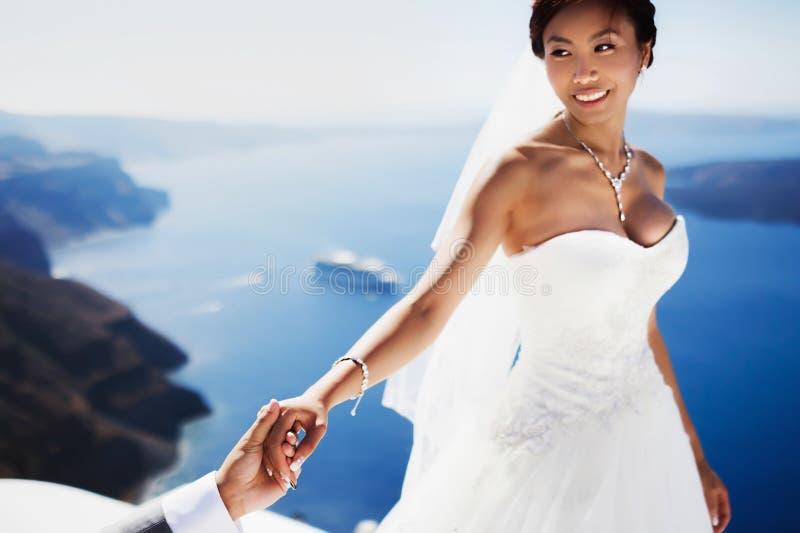 I ricchi alla moda nozze asiatiche sorridenti dello sposo e della sposa esaminano ciascuno fotografia stock