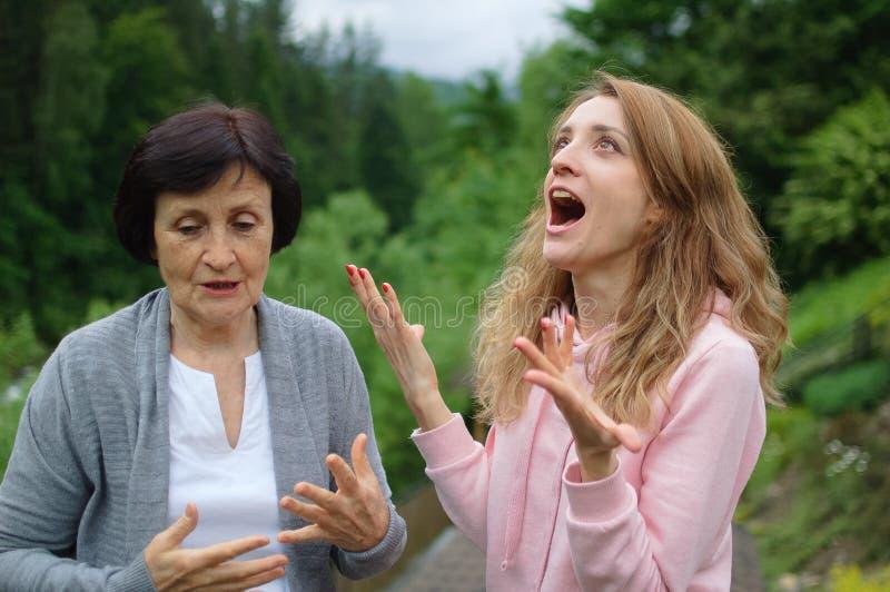 I ritratti all'aperto di madre anziana e figlia adulta comunicano all'esterno del paesaggio delle foreste e delle montagne immagini stock