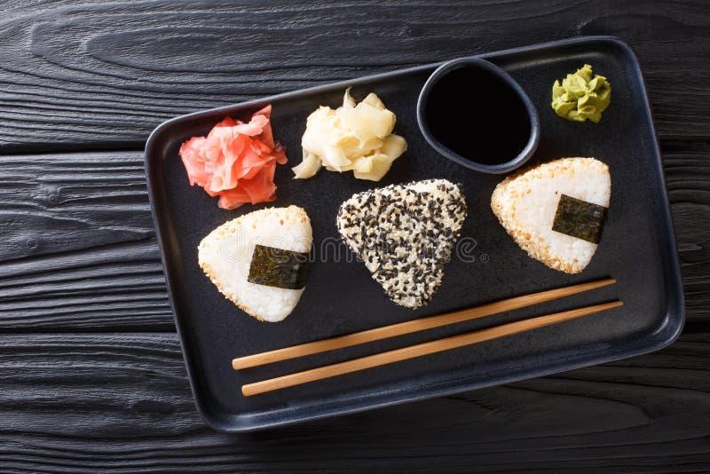 I rotoli di sushi di Onigiri sono servito con il primo piano dello zenzero, del wasabi e della salsa su un piatto vista superiore fotografie stock libere da diritti