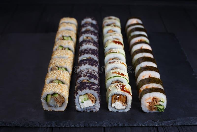I rotoli di sushi tradizionali giapponesi hanno messo con i materiali da otturazione affumicati dell'anguilla sopra fotografia stock