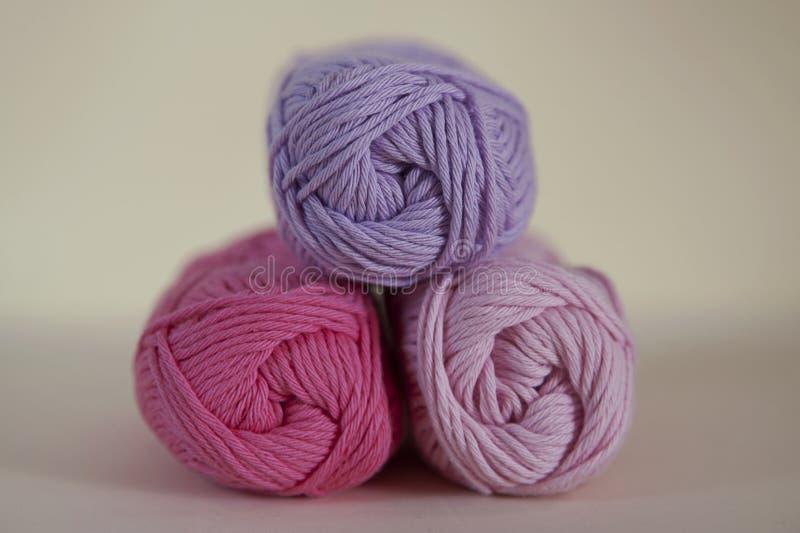 I rotoli rosa di tonalità di filato per lavorano all'uncinetto o tricottano fotografia stock