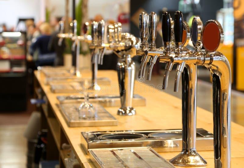 I rubinetti della birra hanno allineato sul contatore di un pub immagini stock