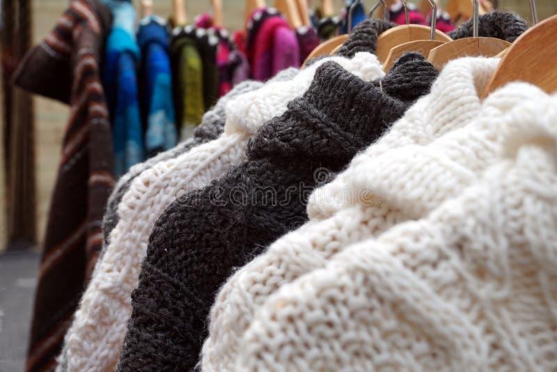 I saltatori ed i rivestimenti tricottati spessi in bianco e nero dell'inverno della lana da vendere su un marlet si bloccano immagine stock libera da diritti