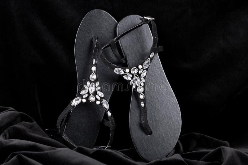 I sandali delle donne di colore eleganti, decorati con le pietre, contro un velluto nero fotografie stock