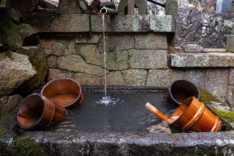 I secchi di legno in una fontana dalla scala all'entrata di Nigatsudo Nigatsu-fanno tempio, parte di Todai-Ji a Nara, Giappone immagini stock