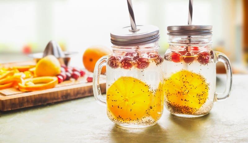 I semi di Chia della prima colazione innaffiano in barattoli di muratore sulla tavola con le fette ed i mirtilli rossi arancio Be fotografie stock