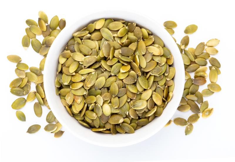I semi di zucca hanno sbucciato i semi nella varia raccolta dei dadi della ciotola bianca fotografie stock libere da diritti