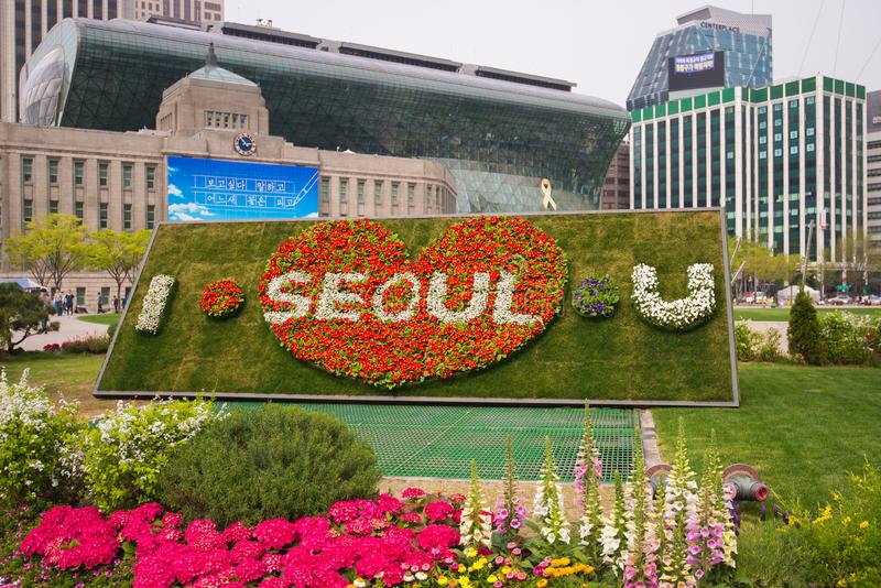 `I Seoul U` sign with beautiful flower in foreground and cityscape in background at City Hall in South Korea. royalty free stock photo