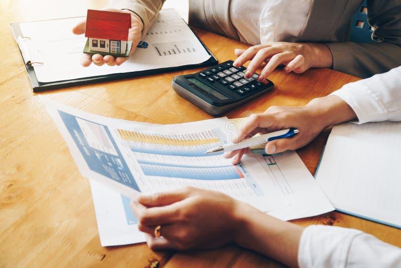 I servizi immobili per la casa d'acquisto tiene il modello della casa ed il pagamento della tavola di calcolazione al cliente immagine stock