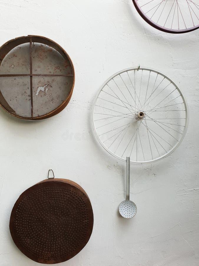 I setacci, le ruote di bicicletta e una siviera hanno appeso su una parete bianca di un TR fotografie stock libere da diritti