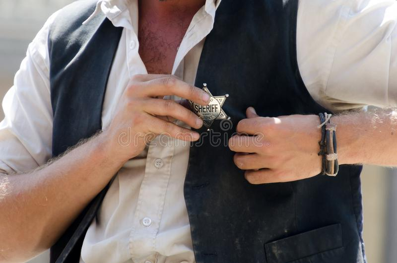 I am the sheriff. A man about to put the sheriff badge with star shape in his vest stock images