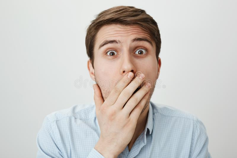I am shocked to bottom of my heart. Portrait of terrified and amazed european male model covering mouth with palm while. Gasping, lifting eyebrows as seeing royalty free stock photography