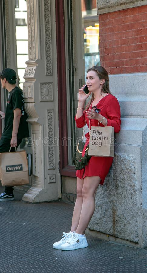 I shopped at Bloomingdale`s. New York, 6/15/2019: Unidentified young lady in a red dress talks on the phone while leaning against a building wall and holding a stock image