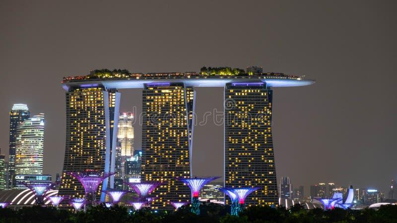 I Singapore på natten sammanfogar byggnaderna eller höghusen tillsammans för att öppna branden för att förhöja skönheten av stade arkivbilder