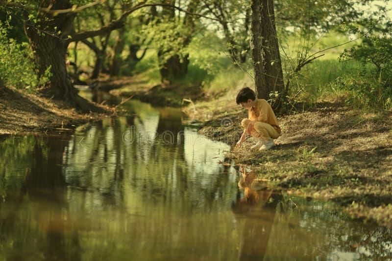 I skogen nära den gulliga pojken för flod royaltyfria foton