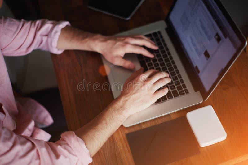 I skottmannens händer som arbetar på datoren royaltyfri bild