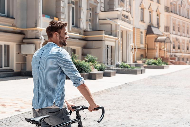 I am a slow walker, but I never walk back.Young brown-haired man standing outdoors with a bicycle and looking away. stock images