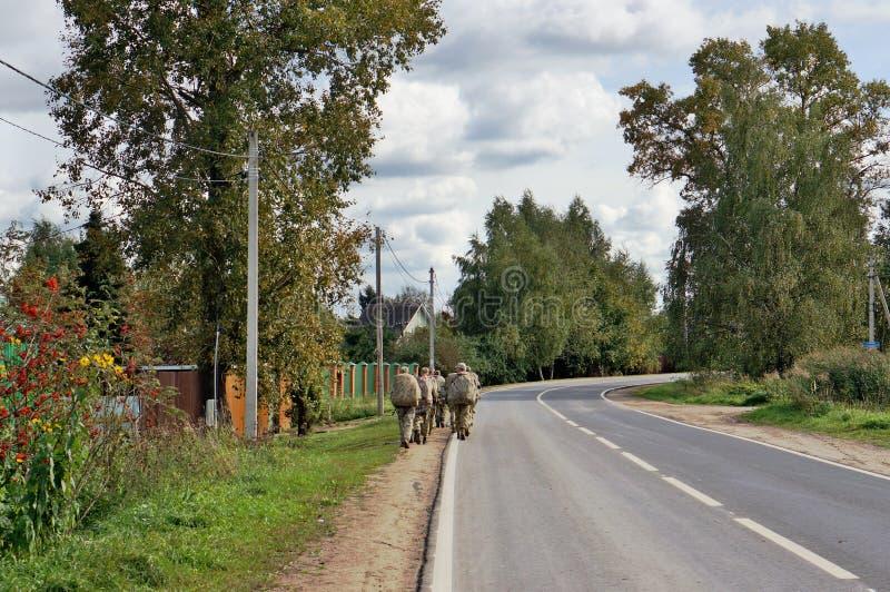 I soldati russi delle forze speciali lasciano la strada del villaggio per il fi fotografia stock