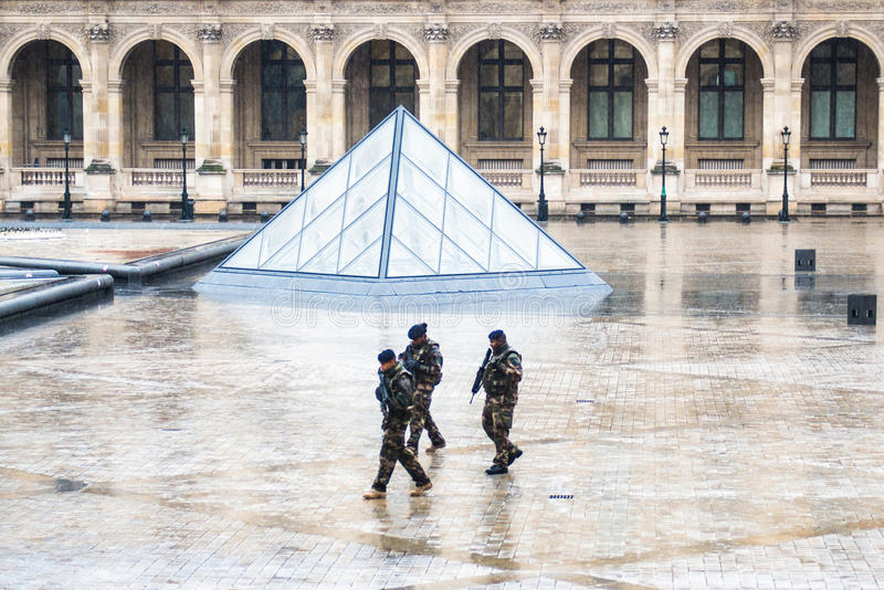 I soldati si avvicinano al museo del Louvre immagini stock