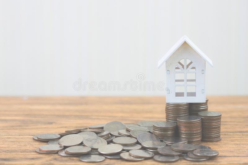 I soldi della pila della moneta aumentano la crescita crescente con la casa bianca di modello sulla tavola di legno immagini stock libere da diritti