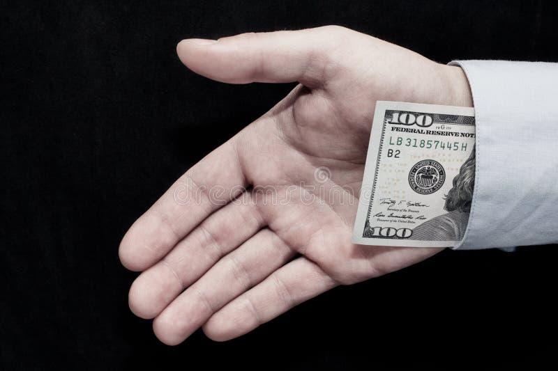 I soldi della tenuta della mano Un criminale serio fotografie stock libere da diritti