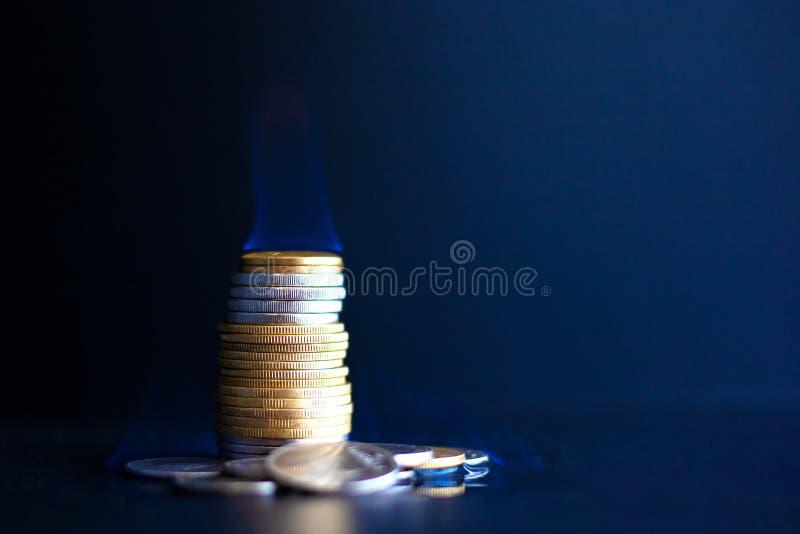 I soldi di concetto si esauriscono rapidamente, monete del metallo bruciano con una fiamma blu fotografia stock