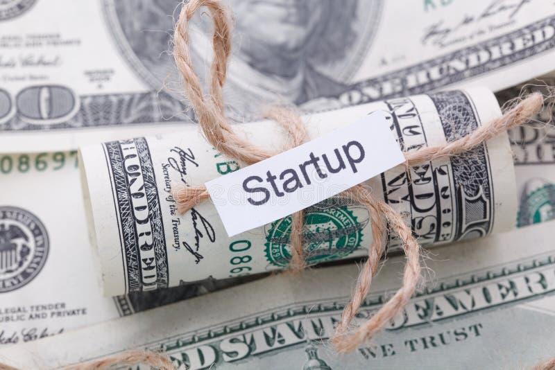 I soldi e l'idea di affari, le banconote in dollari hanno legato con una corda, con un segno - la partenza immagine stock