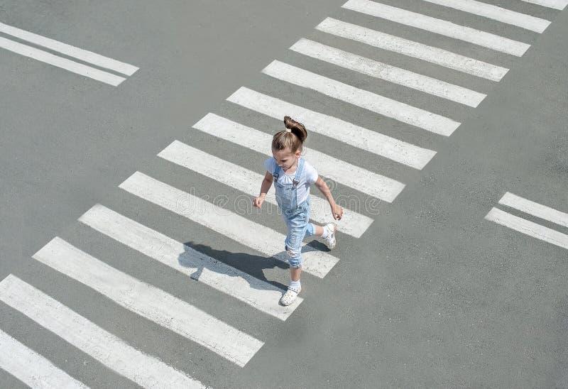 I sommaren på gatan på övergångsstället ungeflicka i modekläder att korsa vägen Fr?n b?sta sikt Skugga på sebran fotografering för bildbyråer