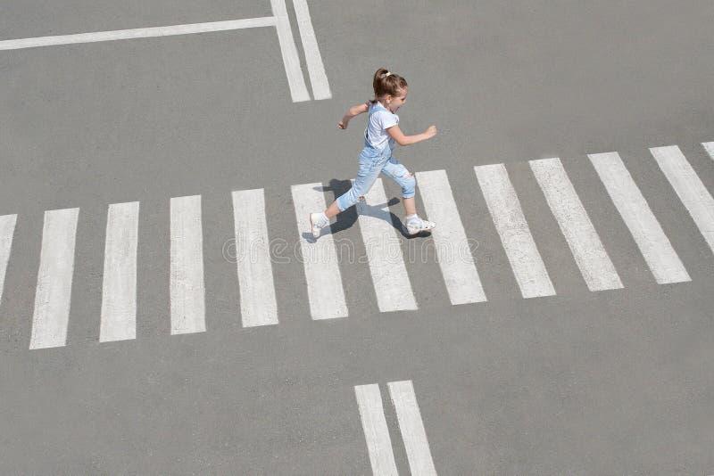 I sommaren på gatan på övergångsstället ungeflicka i modekläder att korsa vägen Fr?n b?sta sikt skugga arkivbilder