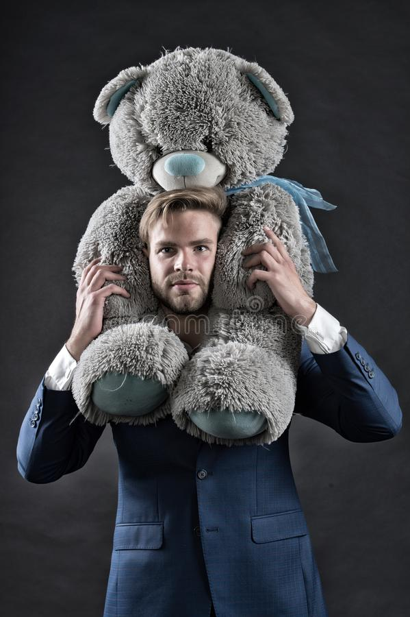 I am so sorry. Man carries giant teddy bear on neck, dark background. Reunion gift concept. Guy calm bearded face with. Toy teddy bear as gesture of reunion or royalty free stock photo