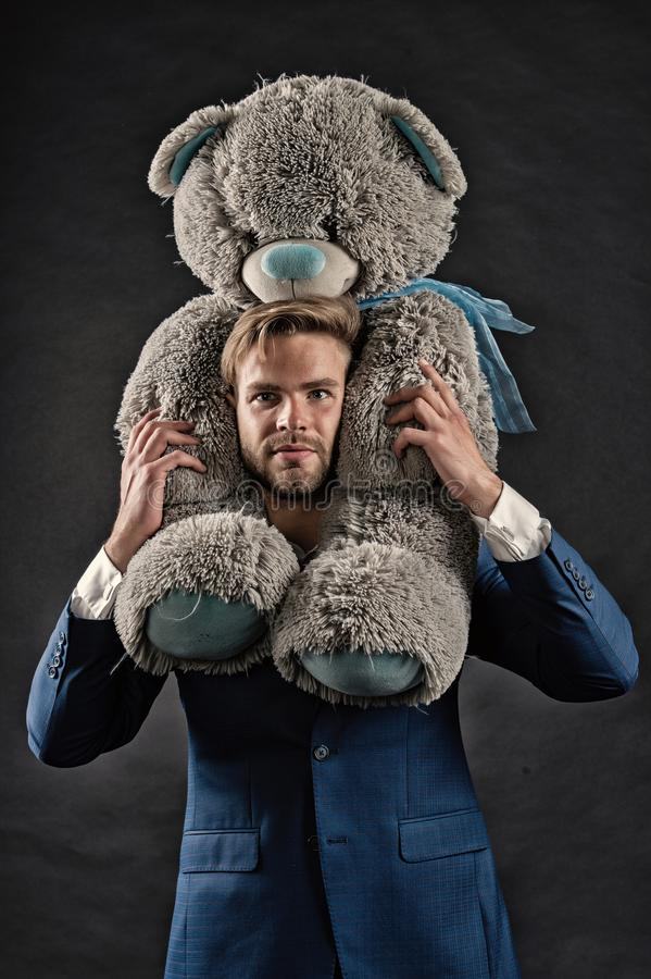 I am so sorry. Man carries giant teddy bear on neck, dark background. Reunion gift concept. Guy calm bearded face with. Toy teddy bear as gesture of reunion or stock photo